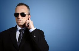 Head and shoulders view of a man in a business suit and sunglasses holding his finger to his ear like a secret service agent on a blue background.